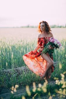 Рыжая девушка в красном платье с букетом пионов, танцы радостное в пшеничном поле летом на закате.