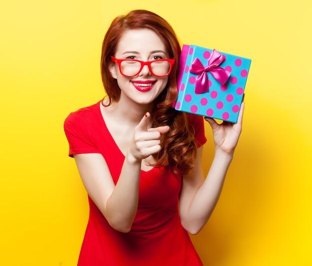 노란색 배경에 안경과 선물 상자가 있는 빨간 드레스를 입은 빨간 머리 소녀