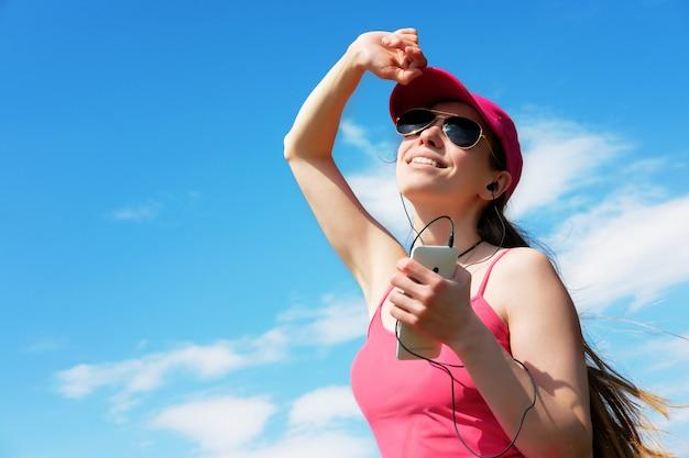 赤毛の女の子は夏、コピースペースでジョギング中に音楽を聴いています