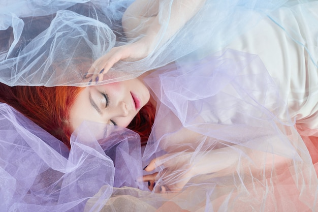 Redhead girl light air colored dress lies on floor