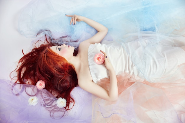 Redhead girl in light airy colored dress lies