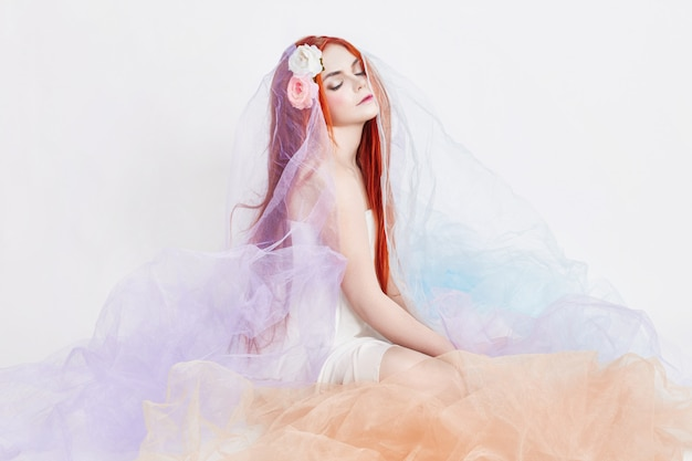 Redhead girl in light airy colored dress sits