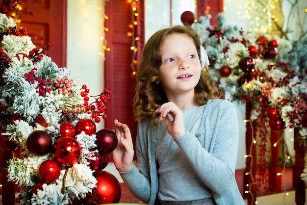 Рыжая девушка на веранде дома, украшенного на рождество