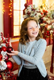 크리스마스 장식 집의 베란다에 빨간 머리 소녀