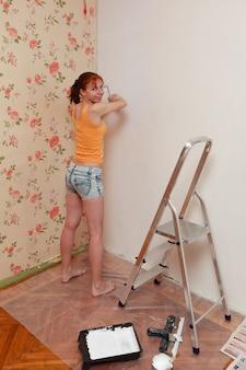 赤毛の少女はアパートの修理中に白い壁をペイントします