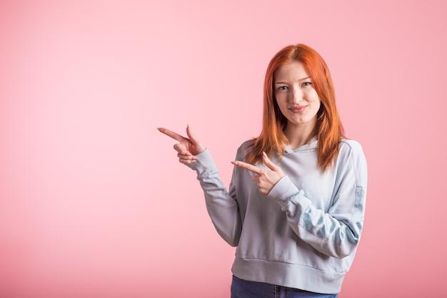 赤毛の女の子はピンクの背景にスタジオのコピースペースの人差し指を横に向けます