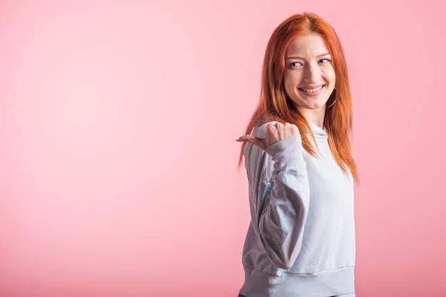 赤毛の女の子はピンクの背景にスタジオのコピースペースのために親指を横に向けます