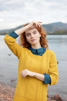 川の近くの赤毛の女の子の肖像画