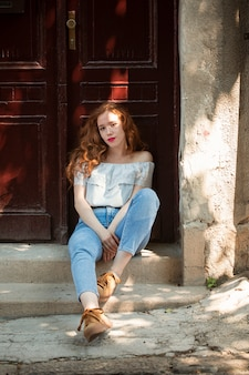 Redhead girl posing in front of a door