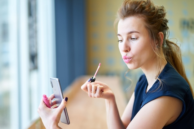 Redhead girl putting on lipstick by herself, watching at reflection at smartphone