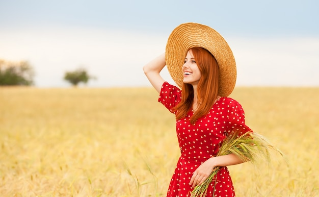 Redhead girl in red dress at wheat field