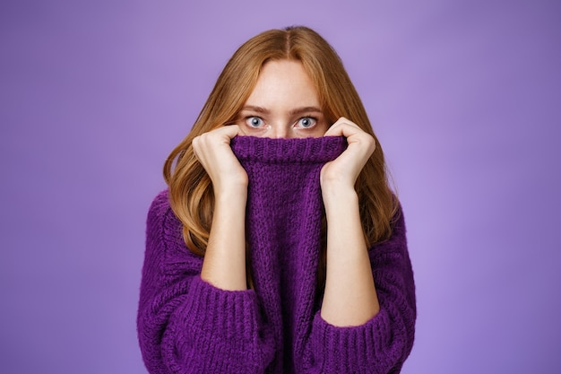 Redhead girl scared winter is comming hiding in collar of warm sweater popping eyes shocked and stunned at camera as if frightened and insecure standing terrified over violet background.