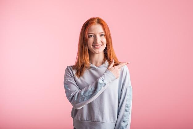 ピンクの背景のスタジオでコピースペースの人差し指を横に示す赤毛の女の子
