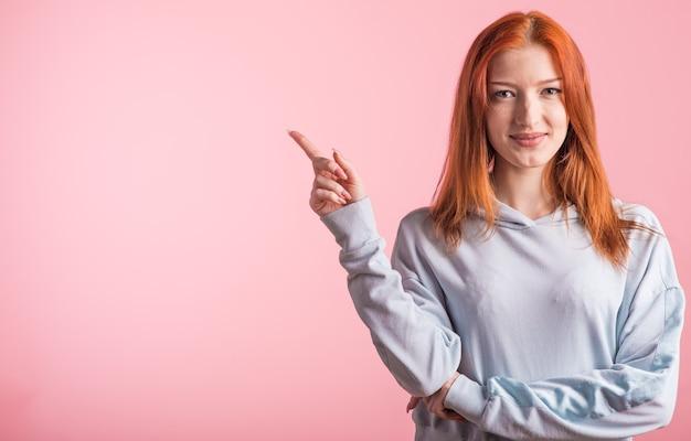 분홍색 배경에 스튜디오에서 copyspace 측면에 검지 손가락을 보여주는 빨간 머리 소녀