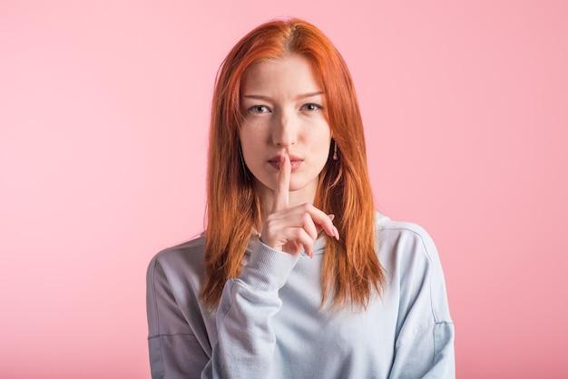 Рыжая девушка показывает жест молчания в студии на розовом фоне