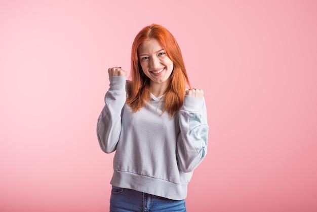 ピンクの背景のスタジオで勝者のジェスチャーを示す赤毛の女の子