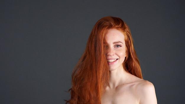 Рыжая девушка улыбается портрет крупным планом. молодая женщина ищет счастливым