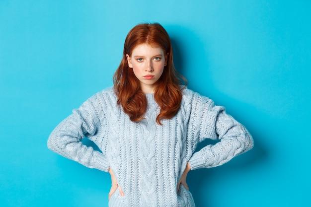 빨간 머리 소녀는 화를 내며 카메라를 쳐다보며 불쾌한 표정을 짓고 화가 나서 파란 배경에 서 있습니다.