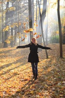 赤毛の少女はぼんやりとした朝に明るい太陽光線の下で紅葉を投げます