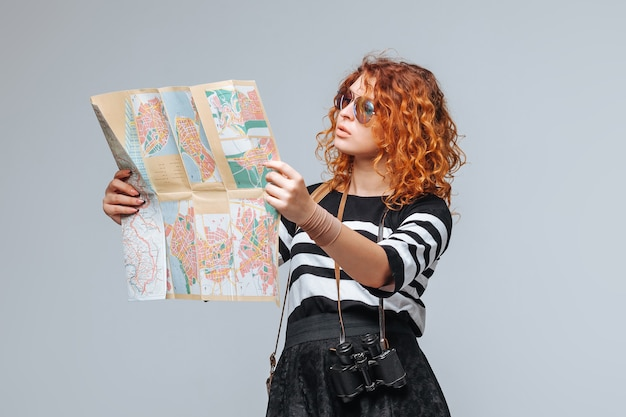 Redhead girl tourist looking at a map