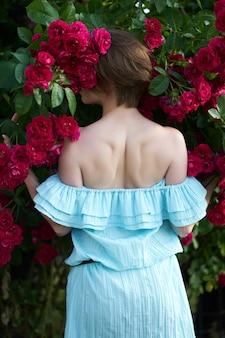 咲くバラの背景にトレンディな青い光のドレスを着ている赤毛の女の子。バラの花に囲まれた女性のポートレート、クローズアップ。後ろから見たところ。