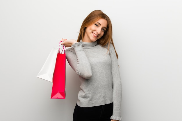 Redhead girl over white wall holding a lot of shopping bags