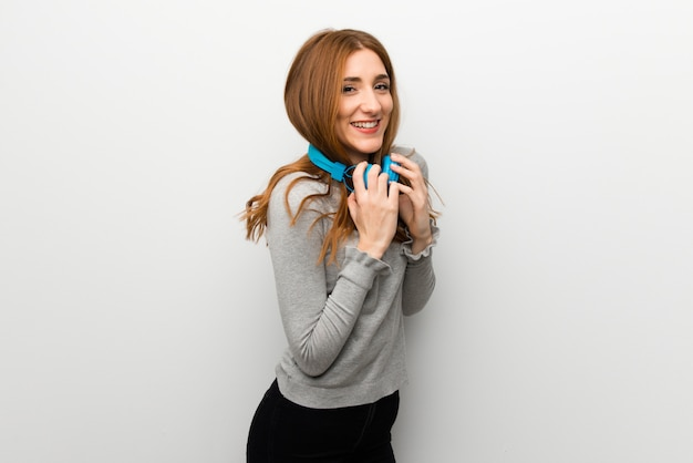 Redhead girl over white wall with headphones