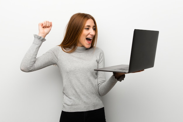 Redhead girl over white wall with laptop and celebrating a victory