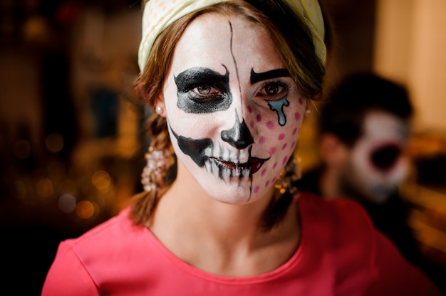 Redhead girl with adorable halloween makeup on the party