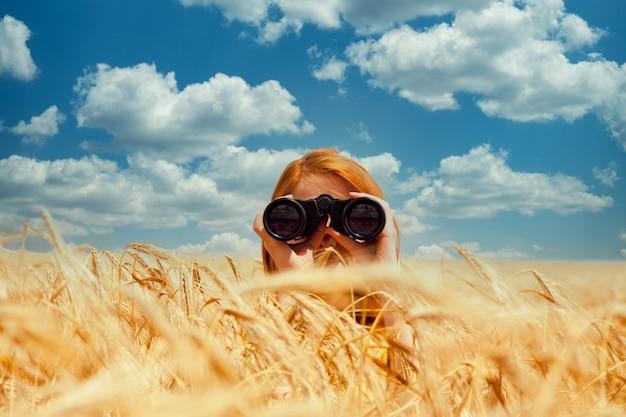 Рыжая девушка с биноклем на пшеничном поле.