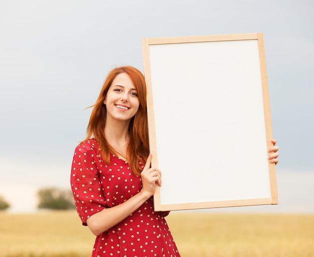 Рыжая девушка с доской на пшеничном поле