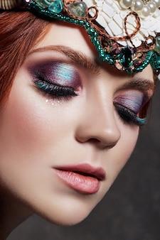 明るい化粧と大きなまつ毛を持つ赤毛の女の子。赤い髪の謎の妖精女。大きな目と色のついた影、長いまつ毛。セクシーな表情、純粋なスキンケア、ケアフェイス