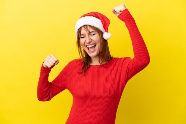 Рыжая девушка в новогодней шапке на желтом фоне празднует победу