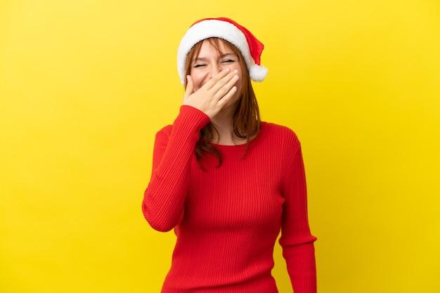 黄色の背景に分離されたクリスマス帽子と赤毛の少女幸せと笑顔の手で口を覆う