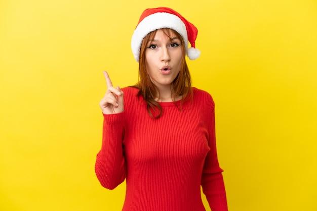 Рыжая девушка в новогодней шапке изолирована на желтом фоне, намереваясь реализовать решение, подняв палец вверх