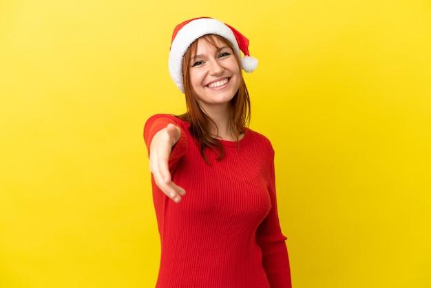 Рыжая девушка в новогодней шапке изолирована на желтом фоне, пожимая руку для заключения хорошей сделки