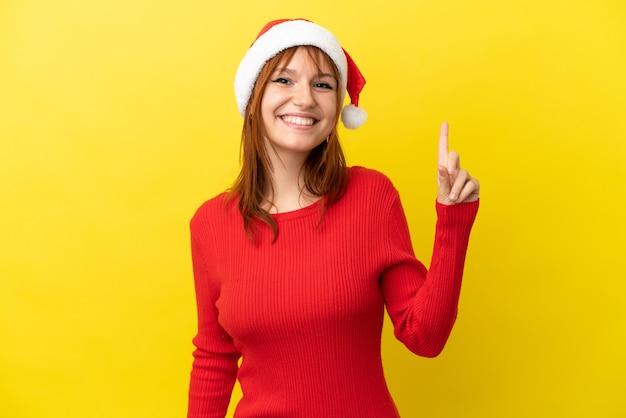 Рыжая девушка в новогодней шапке на желтом фоне показывает и поднимает палец в знак лучших