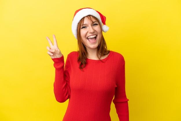 Рыжая девушка в новогодней шапке на желтом фоне улыбается и показывает знак победы