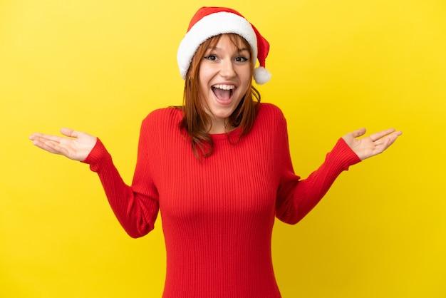 ショックを受けた顔の表情で黄色の背景に分離されたクリスマス帽子と赤毛の少女