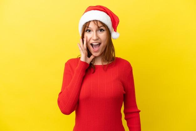 驚きとショックを受けた表情で黄色の背景に分離されたクリスマス帽子と赤毛の少女