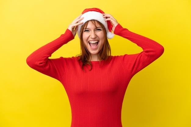 驚きの表現と黄色の背景に分離されたクリスマス帽子と赤毛の少女