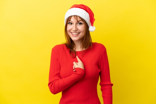 驚きの表情で黄色の背景に分離されたクリスマス帽子と赤毛の少女