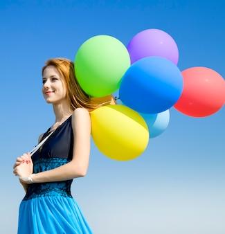 푸른 하늘에 컬러 풍선 빨강 머리 소녀.