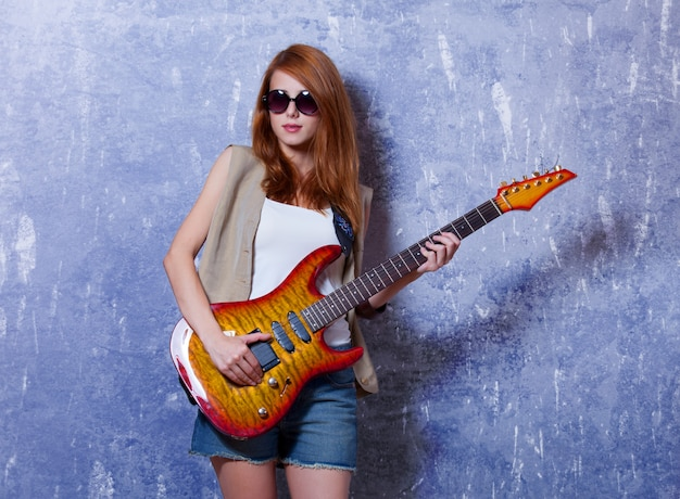 Redhead girl with guitar near wall