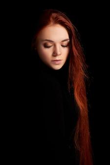 Рыжая девушка с портретом искусства контраста длинных волос. идеальная женщина на черном фоне. шикарные волосы и красивые глаза. естественная красота, чистая кожа, уход за лицом и волосами. сильные и густые волосы