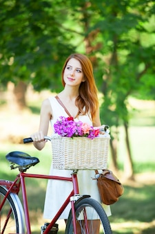 Redhead girl with retro bike in the park.