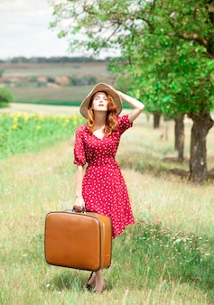 Рыжая девушка с чемоданом на открытом воздухе.