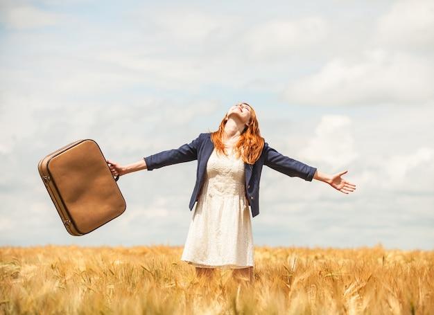 春の麦畑でスーツケースを持った赤毛の少女。