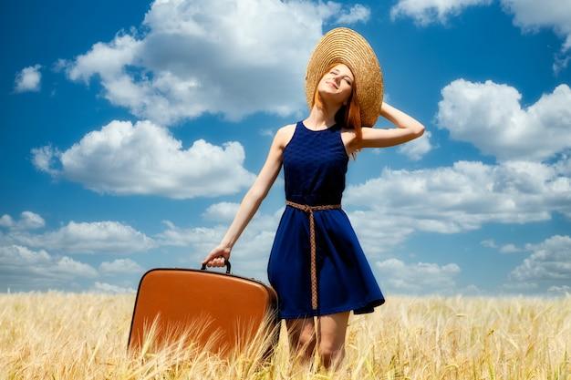 Рыжая девушка с чемоданом на поле яровой пшеницы.