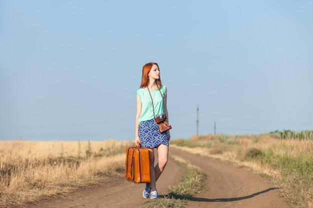 田舎道でスーツケースを持った赤毛の少女。
